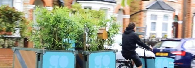 pop-up parklet being towed by bicycle