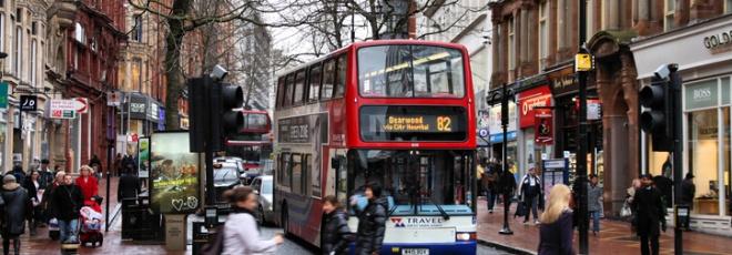 pedestrians cross road in front of bus in birmingham
